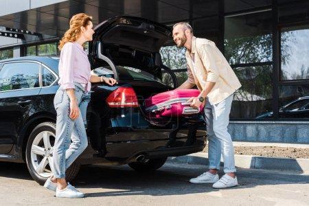 Photo pour Vue bas d'angle de l'homme heureux mettant le bagage rose dans le tronc de voiture près de la femme - image libre de droit