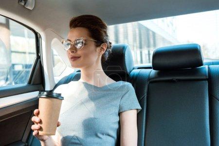 Photo pour Femme d'affaires gaie dans des glaces s'asseyant dans la voiture et retenant la cuvette de papier - image libre de droit