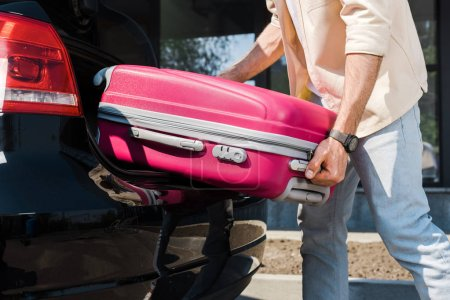 Photo for Cropped view of man putting pink luggage in car trunk - Royalty Free Image