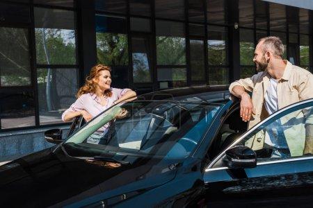 Photo pour Bel homme regardant la femme heureuse tout en restant près de la voiture noire - image libre de droit