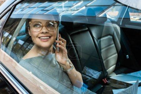 Photo pour Femme d'affaires heureuse dans des glaces regardant la fenêtre tout en parlant sur le smartphone - image libre de droit