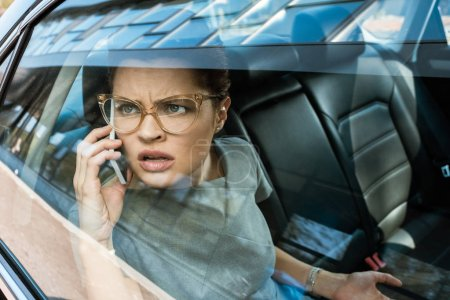 Photo for Displeased businesswoman in glasses looking at window while talking on smartphone - Royalty Free Image