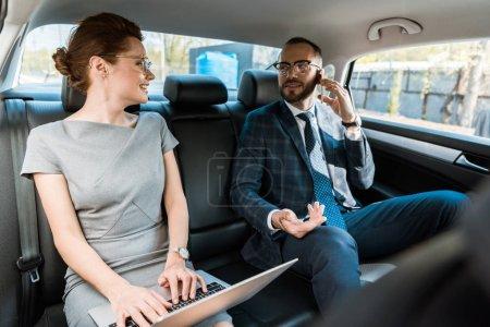Photo pour Foyer sélectif de l'homme d'affaires dans les lunettes parler sur smartphone et regarder la femme d'affaires tapant sur ordinateur portable dans la voiture - image libre de droit