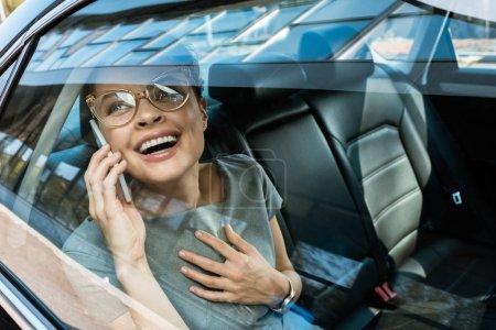 Photo pour Femme heureux dans des glaces riant tout en parlant sur le smartphone dans la voiture - image libre de droit