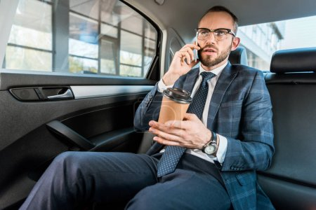 Photo for Low angle view of handsome businessman talking on smartphone and holding paper cup in car - Royalty Free Image