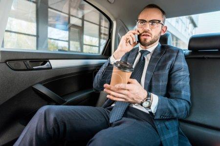 Photo pour Vue basse d'angle de l'homme d'affaires beau parlant sur le smartphone et retenant la tasse de papier dans la voiture - image libre de droit