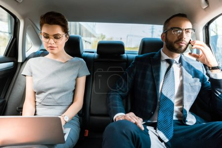 Photo for Attractive businesswoman using laptop near businesswoman talking on smartphone in car - Royalty Free Image