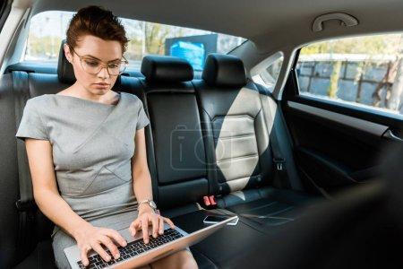 Photo pour Foyer sélectif de belle femme d'affaires dans les lunettes de dactylographie sur ordinateur portable en voiture - image libre de droit