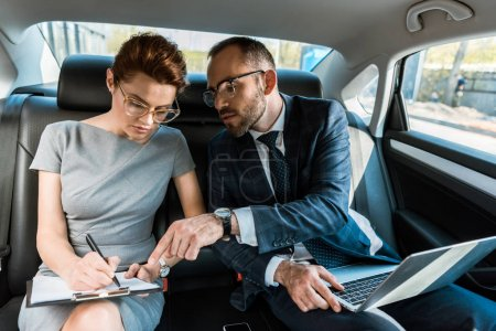 handsome businessman pointing with finger at clipboard while sitting with laptop near woman in car