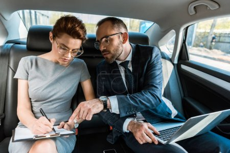 Photo pour Handsome businessman pointing with finger at clipboard while sitting with laptop near woman in car - image libre de droit