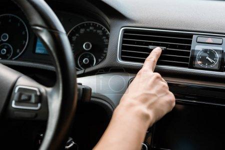 Photo pour Vue recadrée de femme touchant l'interrupteur de climatiseur dans la voiture - image libre de droit