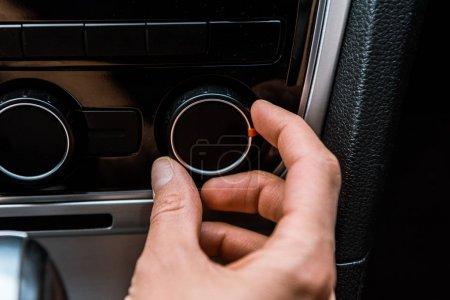 Photo pour Vue recadrée de l'homme touchant bouton de volume dans la voiture - image libre de droit