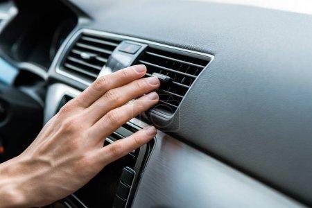 Photo pour Vue recadrée de l'homme touchant l'interrupteur de climatiseur dans la voiture - image libre de droit
