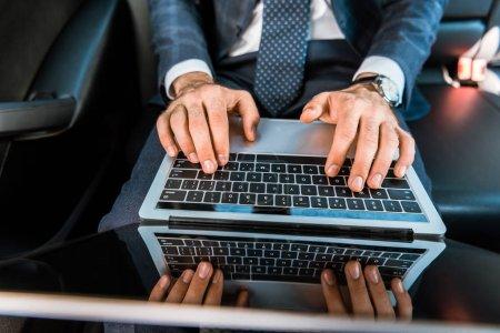 Photo pour Accent sélectif de l'homme d'affaires tapant sur ordinateur portable dans la voiture - image libre de droit
