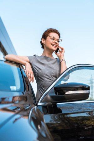 Photo pour Vue basse d'angle de la femme heureuse parlant sur le smartphone près de la voiture noire - image libre de droit