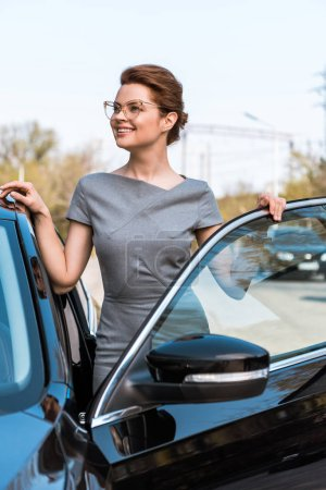 Photo for Happy woman in glasses standing near black car and smiling in parking - Royalty Free Image
