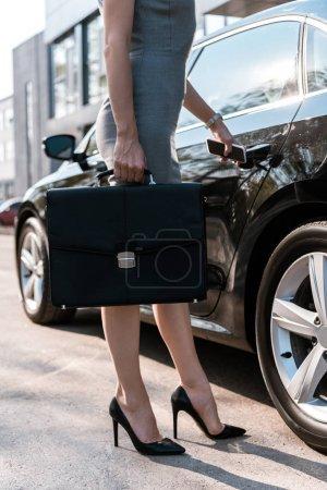 Photo pour Vue recadrée de femme d'affaires debout près de l'automobile noire avec mallette - image libre de droit