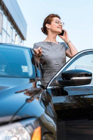 Photo pour Vue bas d'angle de la femme gaie parlant sur le smartphone près de la voiture noire - image libre de droit