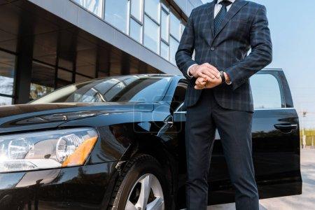 Photo pour Vue recadrée de de l'homme d'affaires touchant montre et debout près de voiture noire - image libre de droit