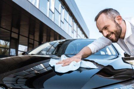 Photo pour Low angle view of happy businessman cleaning black car with white cloth near building - image libre de droit