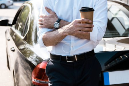 Photo pour Cropped view of man holding paper cup while standing while crossed arms near car - image libre de droit