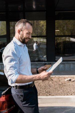 Photo pour Homme d'affaires heureux regardant la carte tout en restant près de la voiture noire - image libre de droit