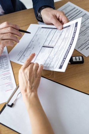 Photo for Cropped view of car dealer showing car loan application form to woman in office - Royalty Free Image