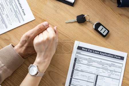 Photo for Cropped view of man and woman holding hands near car key and documents - Royalty Free Image