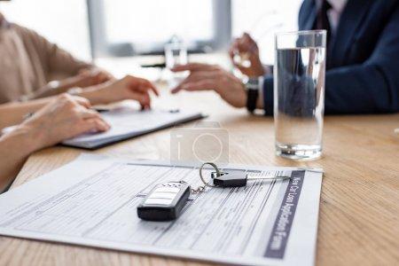 Photo pour Orientation sélective des clés de voiture près de l'accord, verre d'eau, concessionnaire automobile et les clients - image libre de droit