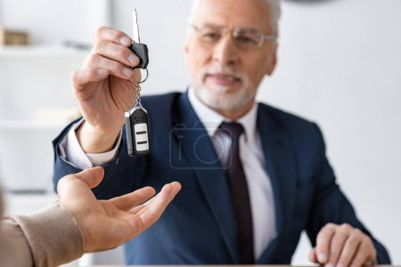 Photo for Selective focus of car dealer giving car key to man in office - Royalty Free Image