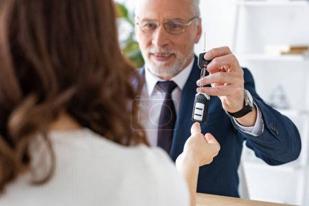 Photo for Selective focus of cheerful car dealer giving car keys to woman - Royalty Free Image