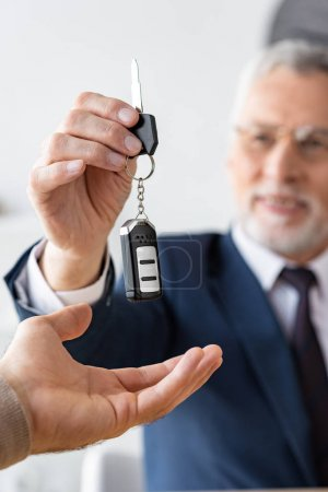 Photo for Selective focus of car dealer in glasses giving car key to man in office - Royalty Free Image