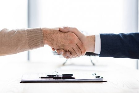 Foto de Cropped view of man and car dealer shaking hands in office - Imagen libre de derechos