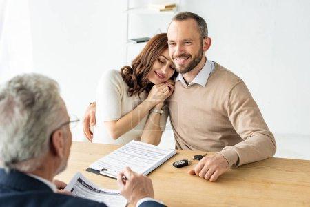 Photo pour Femme heureuse avec les yeux fermés près de l'homme et du revendeur de voiture - image libre de droit