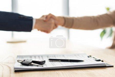 Photo pour Mise au point sélective du presse-papiers, du stylo et de la clé de voiture près des hommes se serrant la main - image libre de droit