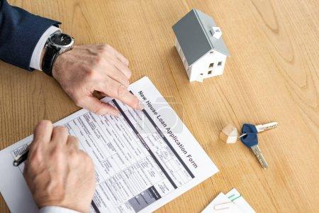 Photo pour Vue recadrée du stylo de fixation de revendeur de maison près du nouveau formulaire de demande de prêt de maison lettrage près du modèle de maison et de la clef - image libre de droit