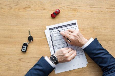 Photo pour Vue supérieure du stylo de fixation de revendeur de voiture près du document avec le nouveau lettrage de forme de formulaire de demande de prêt de voiture, la voiture de jouet et la clef de voiture - image libre de droit