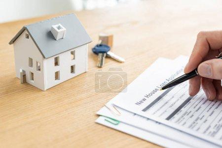 Photo pour Vue recadrée du stylo de fixation de revendeur de maison près du document avec le lettrage de prêt de nouvelle maison, modèle de maison et les clefs - image libre de droit