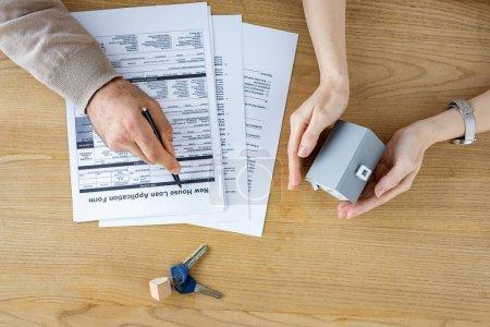 Photo pour Vue supérieure de l'homme retenant le stylo près du nouveau formulaire de demande de prêt de maison et de la femme avec le modèle de maison dans des mains - image libre de droit