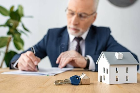 Photo for Selective focus of keys and house model near house dealer in glasses - Royalty Free Image