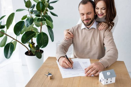 Photo for Handsome man signing contract near happy woman, keys and house model - Royalty Free Image
