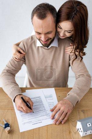 Photo pour Homme heureux retenant le stylo près du document avec le lettrage de contrat de location et la femme gaie - image libre de droit