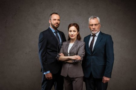 Photo for Attractive businesswoman standing with crossed arms near men on grey - Royalty Free Image