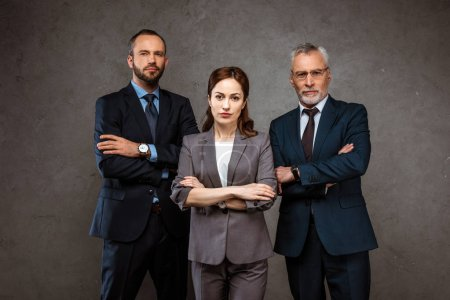 Photo for Attractive businesswoman and handsome businessmen standing with crossed arms on grey - Royalty Free Image