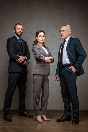 Photo pour Low angle view of beautiful businesswoman standing with crossed arms near handsome businessmen - image libre de droit