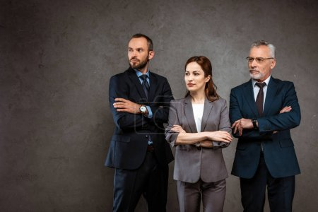 Photo for Successful businesswoman and handsome businessmen standing with crossed arms on grey - Royalty Free Image
