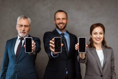Photo pour Selective focus of cheerful businessmen and businesswoman holding smartphones with blank screens on grey - image libre de droit