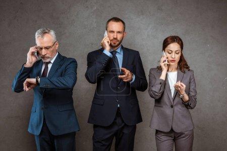 Photo pour Beaux hommes d'affaires parlant sur le smartphone et pointant avec le doigt tout en regardant la caméra près des partenaires sur le gris - image libre de droit
