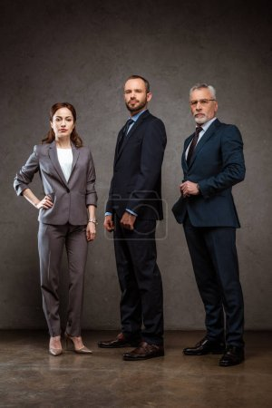 Photo pour Low angle view of businesswoman standing with hand on hip near handsome businessmen on grey - image libre de droit