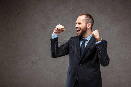 feliz barbudo hombre de negocios en traje gesto mientras se celebra en gris
